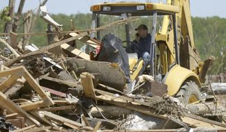 """A dozer pushes storm debris in Vilonia, Ark., Thursday, May 1, 2014, in the wake of a tornado that struck the town late Sunday. Forecasters say a tornado that hit Little Rock's suburbs and killed 15 people had winds approaching 200 mph. Sunday's storm was rated as a """"high-end"""" EF4 on a scale of tornado strength. (AP Photo/Danny Johnston)"""