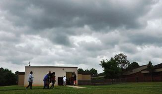 People enter a community storm shelter during a tornado watch in Tuscaloosa, Ala., on in this image taken from video, Tuesday, April 29, 2014. Hundreds of people sought refuge in structures built after the 2011 tornado outbreak during the most recent wave of severe weather to hit the state. (AP Photo/Jay Reeves)