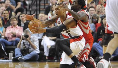 Houston Rockets' Patrick Beverley (2) fouls against Portland Trail Blazers'  Damian Lillard (0) during the first half of game six of an NBA basketball first-round playoff series game in Portland, Ore., Friday May 2, 2014. (AP Photo/Greg Wahl-Stephens)