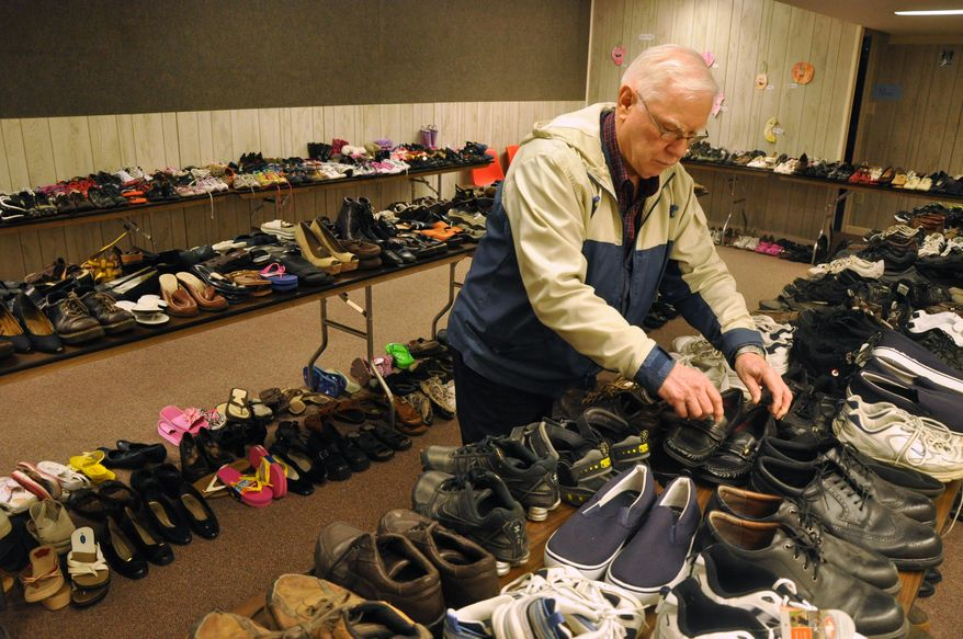 """In an April 28, 2014 photo, LeRoy Koehler organizes shoes prior to the Soul to Sole event at the Beatrice Church of Christ in Beatrice, Neb. """"Sole to Soul,"""" will be held Saturday, May 3, and project manager Linda Lindell said the idea of giving shoes to those in need has been welcomed by both those who donate and those in need of a pair or two. (AP Photo/Beatrice Daily Sun,Scott Koperski)"""