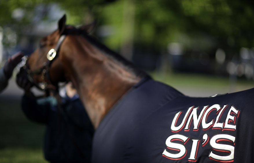 Kentucky Derby entrant Uncle Sigh gets a bath after a morning workout at Churchill Downs Friday, May 2, 2014, in Louisville, Ky. (AP Photo/David Goldman)