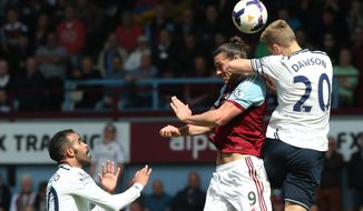 West Ham's Andy Carroll, center, heads the ball under pressure from Tottenham's Michael Dawson, right, during their English Premier League soccer match between West Ham United and Tottenham Hotspur at the Boleyn stadium in London Saturday, May  3  2014. (AP Photo/Alastair Grant)