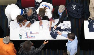 Party volunteers sign in delegates at the South Carolina Democratic Party convention on Saturday, May 3, 2014, in Columbia, S.C. Democrats are encouraging their voters to be optimistic, saying this is the year the party's fortunes will turn in South Carolina. (AP Photo/Jeffrey Collins)