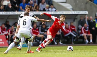 Southampton's Adam Lallana, right, in action against Swansea City's Ashley Williams, front, during their English Premier League soccer match at the Liberty Stadium, Swansea, Wales, Saturday, May 3, 2014. (AP Photo/Chris Ison, PA Wire)    UNITED KINGDOM OUT    -    NO SALES    -   NO ARCHIVES
