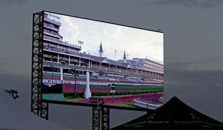A new video screen is seen at sunrise at Churchill Downs Saturday, May 3, 2014, in Louisville, Ky. (AP Photo/Garry Jones)