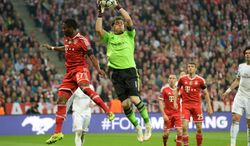 Real goalkeeper Iker Casillas grabs the ball next to Bayern's David Alaba during the Champions League semifinal second leg soccer match between Bayern Munich and Real Madrid at the Allianz Arena in Munich, southern Germany, Tuesday, April 29, 2014. (AP Photo/Kerstin Joensson)