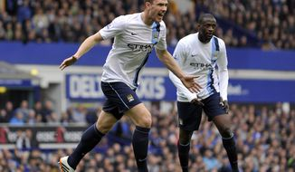 Manchester City's Edin Dzeko, left, celebrates after scoring the second goal of the game during their English Premier League soccer match against Everton at Goodison Park in Liverpool, England, Saturday May 3, 2014. (AP Photo/Clint Hughes)
