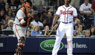 San Francisco Giants catcher Hector Sanchez, left, clenches his fist as Atlanta Braves' Justin Upton, right, strikes out to end the ninth inning of a baseball game Friday, May 2, 2014, in Atlanta. San Francisco won 2-1. (AP Photo/David Tulis)