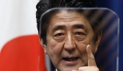 FILE - In this March 20, 2014 file photo, Japanese Prime Minister Shinzo Abe speaks during a press conference at his official residence in Tokyo. Japan is marking the 67th anniversary of its postwar constitution on May 3, 2014 with growing debate over whether to revise the war-renouncing document as Abe pushes for an expanded role for the military. Abe's ruling conservative party has long advocated revision but been unable to sway public opinion. Now he proposes that the government reinterpret the constitution so it can loosen the reins on its military without having to win approval for constitutional change. (AP Photo/Shizuo Kambayash, File)