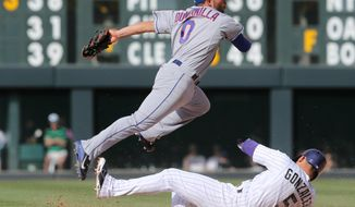 New York Mets shortstop Omar Quintanilla, top, jumps over Colorado Rockies' Carlos Gonzalez after forcing Gonzalez out at second base on the front end of a double play hit into by Nolan Arenado to end the eighth inning of the Mets' 5-1 victory in a baseball game in Denver, Sunday, May 4, 2014. (AP Photo/David Zalubowski)