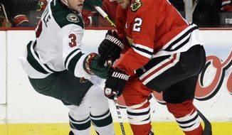 Chicago Blackhawks' Duncan Keith (2), right, controls the puck against Minnesota Wild's Charlie Coyle (3)  during the first period  in Game 2 of an NHL hockey second-round playoff series in Chicago, Sunday, May 4, 2014. (AP Photo/Nam Y. Huh)