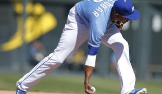 Kansas City Royals shortstop Alcides Escobar fields a ball hit by Detroit Tigers' Austin Jackson during the seventh inning of a baseball game at Kauffman Stadium in Kansas City, Mo., Sunday, May 4, 2014. Jackson was out at first base on the play. (AP Photo/Orlin Wagner)