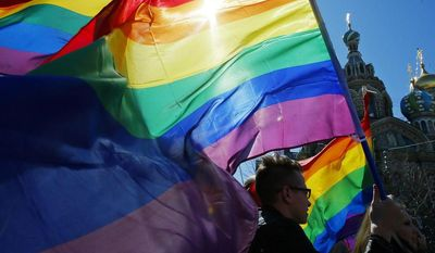 ** FILE ** In this Wednesday, May 1, 2013, file photo, gay rights activists carry rainbow flags as they march during a May Day rally in St. Petersburg, Russia. (AP Photo/Dmitry Lovetsky, File)