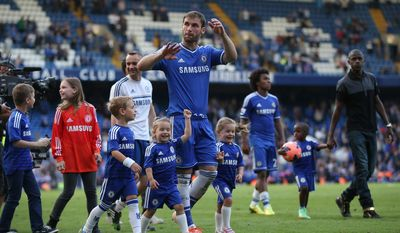 Chelsea's Branislav Ivanovic walks with his children  on the pitch following the English Premier League soccer match between Chelsea and Norwich City at Stamford Bridge stadium in London Sunday, May 4, 2014. The players traditionally walk round the pitch with their family after the last home game of the season. (AP Photo/Alastair Grant)