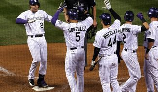 From left, Colorado Rockies' Nolan Areando, left, is congratulated by teammates Carlos Gonzalez, Ryan Wheeler and Troy Tulowitzki as he steps on home plate after hitting a grand slam against the New York Mets in the fifth inning of a baseball game in Denver, Saturday, May 3, 2014. (AP Photo/David Zalubowski)