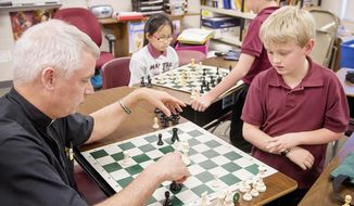 ADVANCED FOR RELEASE SUNDAY, MAY 4, 2014 - Father Brian Connor, left, moves a piece during a chess match with third grader Justin Kirkman during chess club practice on Wednesday, April 9, 2014, at the North American Martyrs Catholic School. Jacey Tran and Cole Hardy contemplate their next moves as they start a match near the end of the practice period. (AP Photo/Lincoln Journal Star, Francis Gardler)