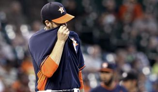 Houston Astros starting pitcher Collin McHugh wipes his face after giving up four runs to the Seattle Mariners in the third inning of a baseball game Sunday, May 4, 2014, in Houston. (AP Photo/Pat Sullivan)