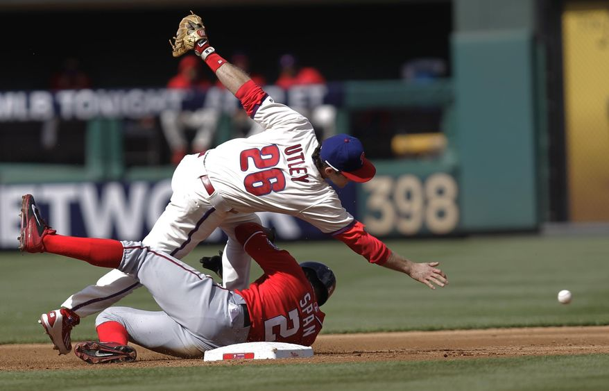 Washington Nationals' Denard Span, bottom, is safe at second as Philadelphia Phillies' Chase Utley bobbles the throw to first on a hit by Nationals' Jayson Werth in the third inning of a baseball game on Sunday, May 4, 2014, in Philadelphia. (AP Photo/Laurence Kesterson)