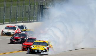 David Ragan (34) moves out of the lane as his car is engulfed in smoke during the NASCAR Aaron's 499 Sprint Cup series auto race at Talladega Superspeedway, Sunday, May 4, 2014, in Talladega, Ala. (AP Photo/Greg McWilliams) ** FILE **