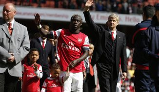 Arsenal's manager Arsene Wenger, center right, and Bacary Sagna, center left, wave to the supporters as the team parade around the stadium in their last home match of the season, after their English Premier League soccer match against West Bromwich Albion at Emirates Stadium in London, Sunday, May 4, 2014. (AP Photo/Sang Tan)