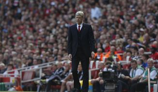 Arsenal's manager Arsene Wenger watches his team play against West Bromwich Albion during their English Premier League soccer match at Emirates Stadium in London, Sunday, May 4, 2014. (AP Photo/Sang Tan)