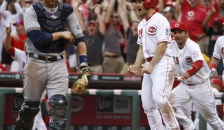 Cincinnati Reds' Chris Heisey (28) reacts after scoring at home plate on a Todd Frazier double hit off Milwaukee Brewers relief pitcher Tyler Thornburg in the tenth inning of a baseball game on Sunday, May 4, 2014, in Cincinnati. Brewers catcher Jonathan Lucroy, left, walks off the field. The Reds won 4-3. (AP Photo/David Kohl)