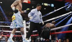 Marcos Maidana, left, from Argentina, watches after knocking Floyd Mayweather Jr. through the ropes in their WBC-WBA welterweight title boxing fight Saturday, May 3, 2014, in Las Vegas. At center is referee Tony Weeks. (AP Photo/Eric Jamison)