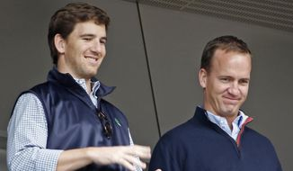 Denver Broncos quarterback Peyton Manning, right, and his brother, New York Giants quarterback Eli Manning, watch from New York Yankees' Derek Jeter's suite during a baseball game between the Yankees and the Tampa Bay Rays at Yankee Stadium in New York, Sunday, May 4, 2014. (AP Photo/Kathy Willens) ** FILE **
