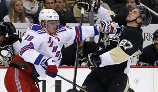 New York Rangers' Marc Staal (18) stiff arms Pittsburgh Penguins' Sidney Crosby (87) off the puck in the second period of game 2 of a second-round NHL playoff hockey series in Pittsburgh Sunday, May 4, 2014. (AP Photo/Gene J. Puskar)