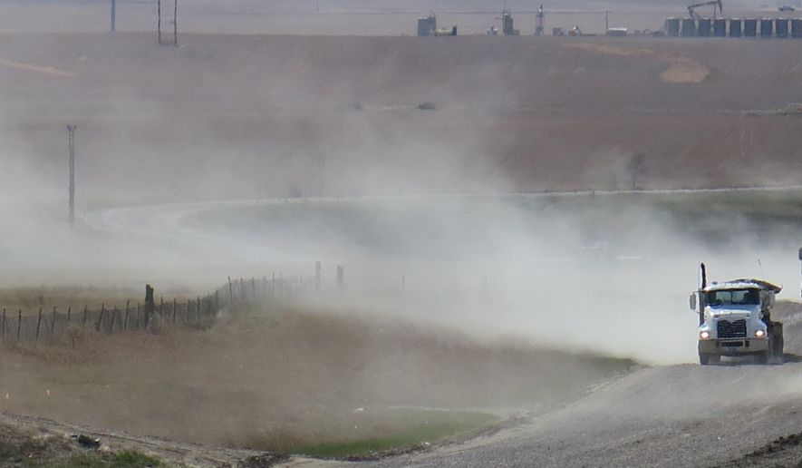 A cloud of dust trails a semitrailer on an unpaved road in Williston, N.D., on Saturday, May 3, 2014. Unpaved roads are essential to North Dakota's oil industry, but controlling the dust they produce can be difficult and expensive. (AP Photo/Josh Wood)