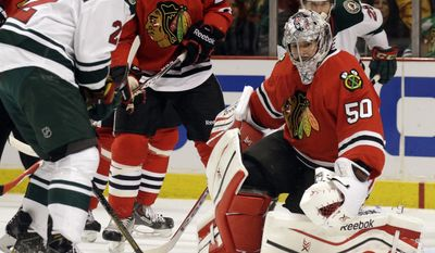 Chicago Blackhawks goalie Corey Crawford (50), right, blocks a shot by Minnesota Wild's Nino Niederreiter (22) during the first period  in Game 2 of an NHL hockey second-round playoff series in Chicago, Sunday, May 4, 2014. (AP Photo/Nam Y. Huh)