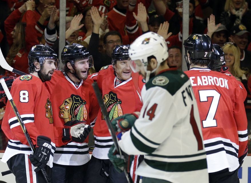 Chicago Blackhawks' Brandon Saad, second from left, celebrates with Nick Leddy (8), Marian Hossa (81) and Brent Seabrook (7) after scoring his goal as Minnesota Wild's Justin Fontaine (14) reacts as he looks down during the second period in Game 2 of an NHL hockey second-round playoff series in Chicago, Sunday, May 4, 2014. (AP Photo/Nam Y. Huh)