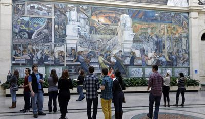 FILE - In this Dec. 10, 2013, file photo, visitors look at the Detroit Industry murals created by Mexican artist Diego Rivera at the Detroit Institute of Arts in Detroit. The DIA announced Monday, May 5, 2014, that it is planning an exhibition next year that focuses on the year that Rivera and his artist wife Frida Kahlo spent in the city. (AP Photo/Carlos Osorio, File)