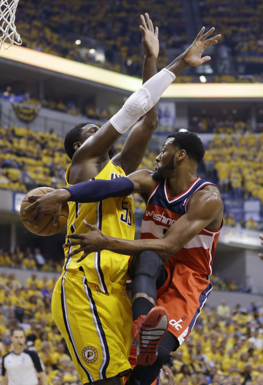 Washington Wizards' John Wall (2) makes a pass against Indiana Pacers' Roy Hibbert (55) during the first quarter of game 1 of the Eastern Conference semifinal NBA basketball playoff series in Indianapolis, Monday, May 5, 2014(AP Photo/Michael Conroy)