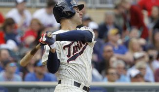 Minnesota Twins' Joe Mauer watches the flight of his 3-run home run off Baltimore Orioles pitcher Brad Brach during the seventh inning of a baseball game in Minneapolis, Saturday, May 3, 2014. The Twins won 6-1.(AP Photo/Ann Heisenfelt)