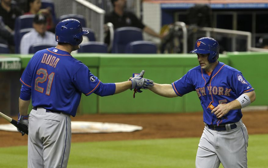 New York Mets' David Wright (5) is congratulated by teammate Lucas Duda (21) after Wright scored on a sacrifice fly by Bobby Abreu against the Miami Marlins during the fourth inning of a baseball game in Miami, Monday, May 5, 2014. (AP Photo/Alan Diaz)