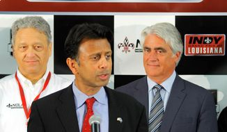 NOLA Motorsports owner Laney Chouest, left and Mark Miles, CEO of IndyCar, right, listen as Louisiana Governor Bobby Jindal announces during a press conference Monday, May 5, 2014,  that IndyCar will race at NOLA Motorsports Park in Avondale next year. (AP Photo/ NOLA.com The Times-Picayune David Grunfeld)