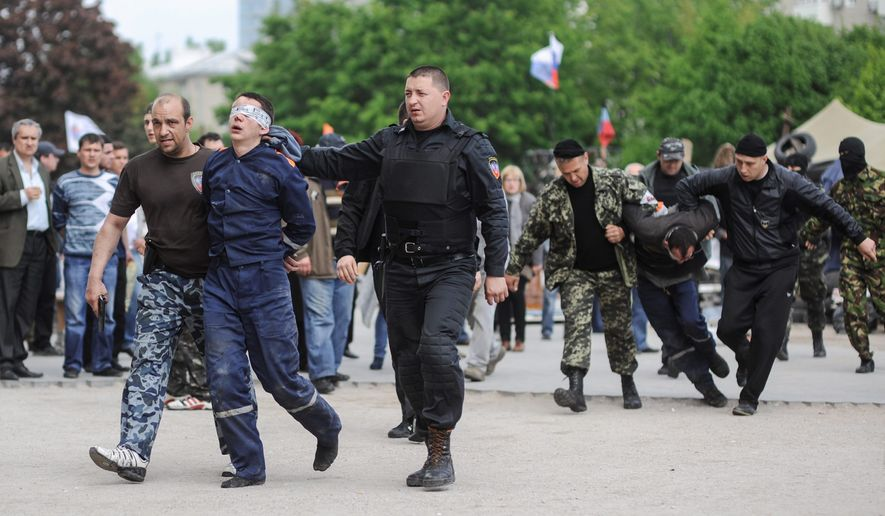 Roundup for Russia: Militants march Ukrainian state employees away from the regional administration building in Donetsk on Monday, continuing their campaign of seizing and ransacking government buildings across restive eastern Ukraine. (ASSOCIATED PRESS)