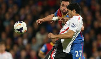 Crystal Palace's Damien Delaney, background,  challenges Liverpool's Luis Suarez during the English Premier League soccer match between Crystal Palace and Liverpool at Selhurst Park stadium in London, Monday, May 5, 2014. (AP Photo/Alastair Grant)