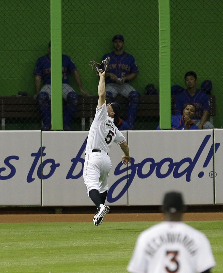Miami Marlins left fielder Reed Johnson (5) catches a fly ball hit by New York Mets' Omar Quintanilla during the fifth inning of a baseball game in Miami, Monday, May 5, 2014. (AP Photo/Alan Diaz)