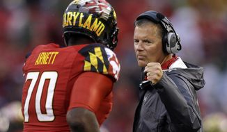 FILE - In this Sept. 21, 2013 file photo, Maryland head coach Randy Edsall, right, fist-bumps offensive linesman De'Onte Arnett who jogs off the field in the first half of an NCAA college football game against West Virginia,  in Baltimore. Maryland begins Big Ten play this season with a schedule that includes Ohio State, Michigan, Wisconsin and Michigan State. (AP Photo/Patrick Semansky, File)