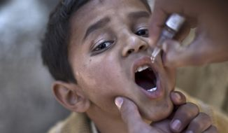 ** FILE ** In this file photo dated Monday Nov. 25, 2013, a Pakistani child is vaccinated against polio by a health worker in Islamabad, Pakistan, Monday, Nov. 25, 2013. (AP Photo/Muhammed Muheisen, FILE)