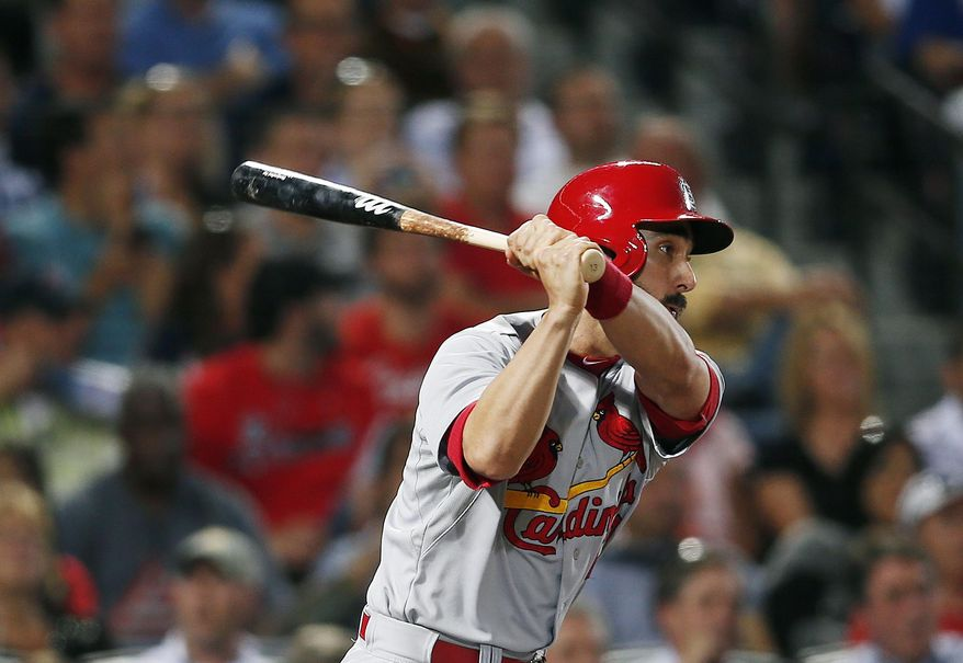 St. Louis Cardinals third baseman Matt Carpenter (13) follows through with a two-run double in the fifth inning of a baseball game against the Atlanta Braves Monday, May 5, 2014 in Atlanta.  (AP Photo/John Bazemore)