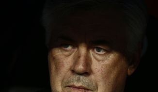 Real Madrid's coach Carlo Ancelotti from Italy sits on the bench during a Spanish La Liga soccer match between Real Madrid and Valencia at the Santiago Bernabeu stadium in Madrid, Spain, Sunday May 4, 2014. (AP Photo/Daniel Ochoa de Olza)