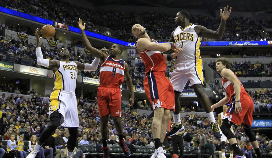 Indiana Pacers' Lance Stephenson (1) makes a pass to Roy Hibbert (55) as Washington Wizards' Marcin Gortat (4) and Martell Webster (9) watch during the second half of an NBA basketball game Friday, Nov. 29, 2013, in Indianapolis. Indiana won 93-73. (AP Photo/Darron Cummings)
