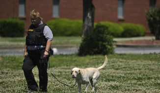 A law enforcement official searches the Paine College campus as it is on lockdown on Monday, May 5, 2014, in Augusta, Ga. The second shooting in two days at a Georgia college Monday left a student with a life-threatening gunshot wound to the head and prompted authorities to pledge to bolster security at the school. (AP Photo/The Augusta Chronicle ,Jon-Michael Sullivan)