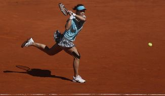 Na Li from China returns the ball during a Madrid Open tennis tournament match against Kirsten Flipkens from Belgium, in Madrid, Spain, Monday, May 5, 2014. (AP Photo/Andres Kudacki)