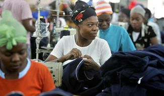 FILE - In this Jan. 31, 2006 file photo, Cylette Senatus, center, assembles a zipper on an athletic jacket, alongside dozens of other skilled seamstresses, at the AG Textile factory, in Port au Prince. Haiti raised slightly its minimum wage for the estimated 29,000 workers who sew together T-shirts and other clothing in the country's apparel factories. President Michel Martelly, his prime minister and a Cabinet member who oversees labor conditions signed the 12.5 percent increase into law. It took effect Thursday, May 1, 2014. (AP Photo/Brennan Linsley)