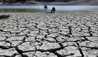 ** FILE ** This March 13, 2014, file photo shows cracks in the dry bed of the Stevens Creek Reservoir in Cupertino, Calif. The Obama administration is more certain than ever that global warming is changing Americans' daily lives and will worsen. (AP Photo/Marcio Jose Sanchez, File)
