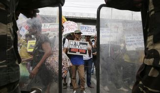 Protesters shout slogans as they picket the headquarters of the Armed Forces of the Philippines to coincide with the opening ceremony of the joint U.S.-Philippines military exercise dubbed Balikatan 2014, Monday, May 5, 2014 at suburban Quezon city, northeast of Manila, Philippines. More than 5,000 U.S. and Filipino troops have begun two weeks of military exercises to flex their muscle in jointly dealing with potential crisis in the Philippines, which is prone to natural disasters and has been locked in a dangerous standoff with China over a disputed shoal. This year's war games focuses on maritime security. (AP Photo/Bullit Marquez)